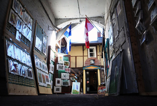 A variety of prints, paintings, and postcards are hung in the alleyway. The cases close at night tolook like French windows.