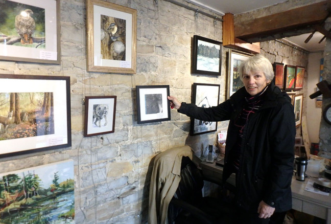Chris Perry stands with her graphite drawing of a raven, whose curious, intelligent eye drawsattention from viewers.