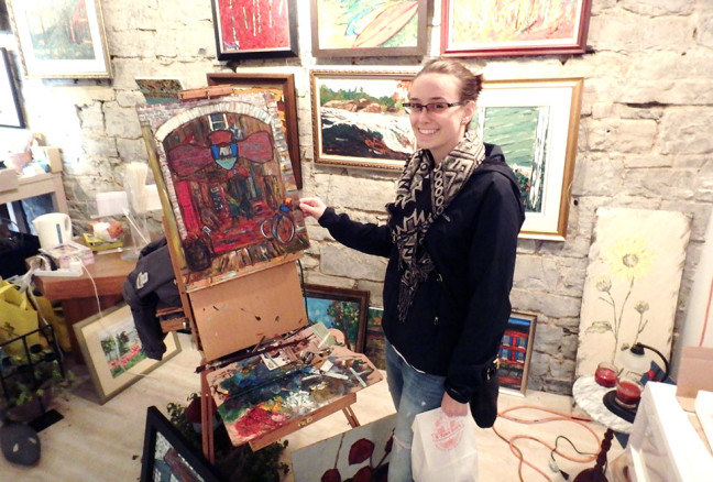 Queens student Elizabeth Gibson Crowder stands next to a painting-in-progress by DavidDossett.