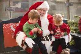 Two children sit on Santa's knees